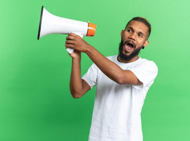 緑の背景の上に感情的で幸せな立っているメガホンを保持している白いtシャツのアフリカ系アメリカ人の若い男