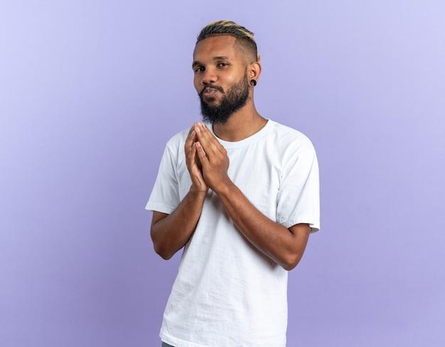 Афро-американский молодой человек в белой футболке держит ладони вместе, весело улыбаясь