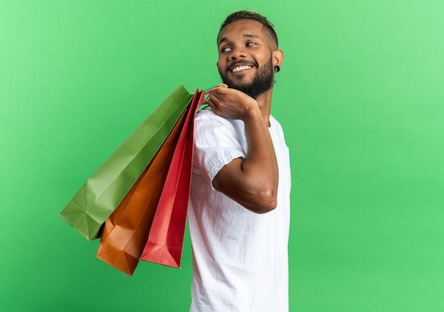 Афро-американский молодой человек в белой футболке держит бумажные пакеты, глядя в сторону, весело улыбаясь и улыбаясь, стоя на зеленом фоне