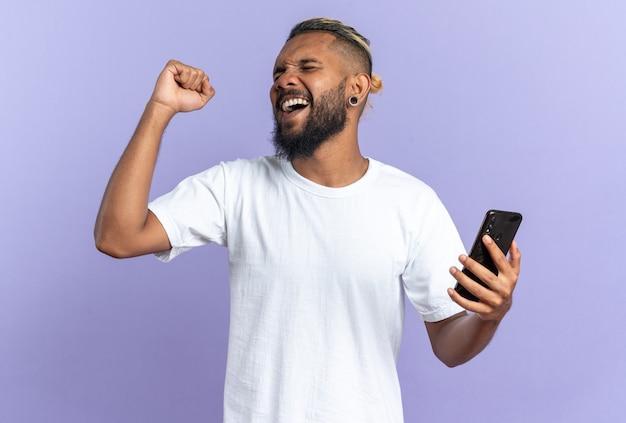 スマートフォンを握りこぶしを握っている白いtシャツを着たアフリカ系アメリカ人の若い男は、彼の成功を喜んで幸せで興奮している