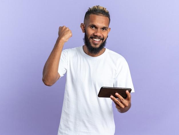 스마트폰을 꽉 쥐고 있는 흰색 티셔츠를 입은 아프리카계 미국인 청년은 파란색 배경 위에 서서 성공을 기뻐하고 기뻐하고 흥분했습니다.