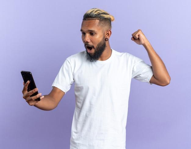 青い背景の上に立って彼の成功を喜んで叫んで幸せで興奮した拳を握りしめスマートフォンを保持している白いtシャツのアフリカ系アメリカ人の若い男
