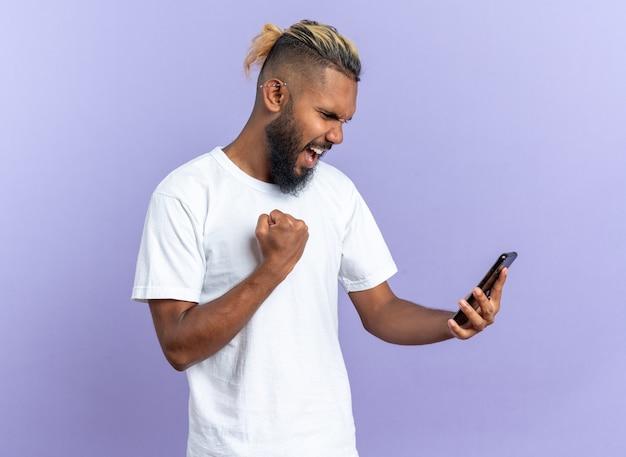 スマートフォンを握りこぶしを握って幸せな白いtシャツのアフリカ系アメリカ人の若い男