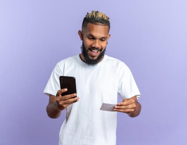 흰색 티셔츠를 입은 아프리카계 미국인 청년이 스마트폰을 들고 파란색 배경 위에 서서 신용카드를 보고 행복하고 놀랐습니다.