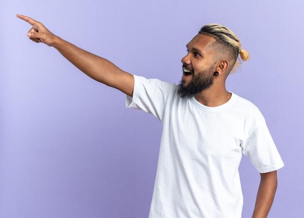 흰색 티셔츠를 입은 아프리카계 미국인 청년은 파란색 배경 위에 서 있는 무언가를 검지 손가락으로 가리키며 행복하고 쾌활한 모습을 바라보고 있습니다.