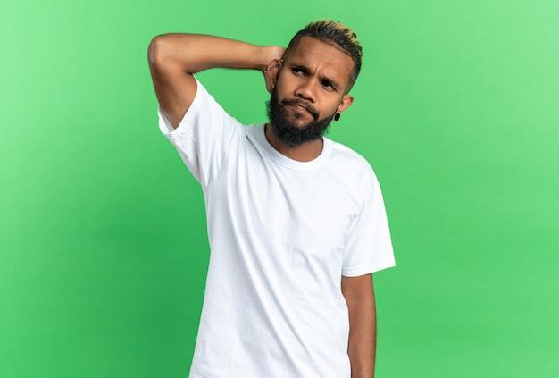 緑の背景の上に立っている彼の頭の上の手で困惑して脇を探している白いtシャツのアフリカ系アメリカ人の若い男