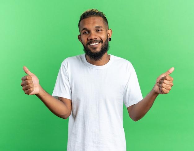 카메라를 행복 하 고 쾌활 한 광범위 하 게 웃 고보고 흰색 티셔츠에 아프리카 계 미국인 젊은 남자
