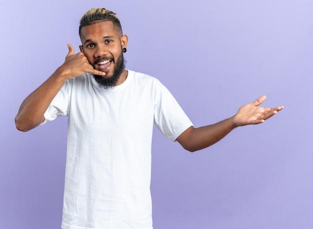 흰색 티셔츠에 아프리카 계 미국인 젊은 남자가 유쾌하게 행복하고 긍정적 인 미소 짓는 카메라를보고 제스처 전화