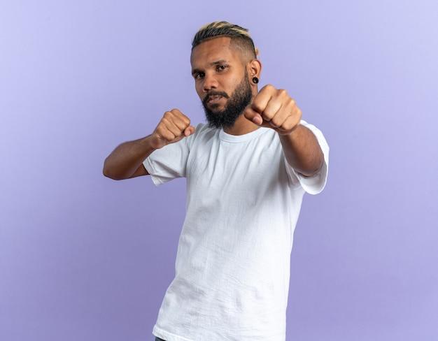 흰색 티셔츠에 아프리카 계 미국인 젊은 남자가 권투 선수처럼 주먹을 쥐고 자신감이 포즈 미소를 카메라를보고