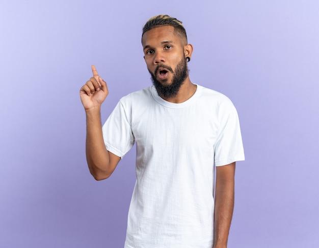 흰색 티셔츠를 입은 아프리카계 미국인 청년이 파란 배경 위에 서 있는 새로운 멋진 아이디어를 가진 검지 손가락을 보여주는 카메라를 보고 놀랐습니다.