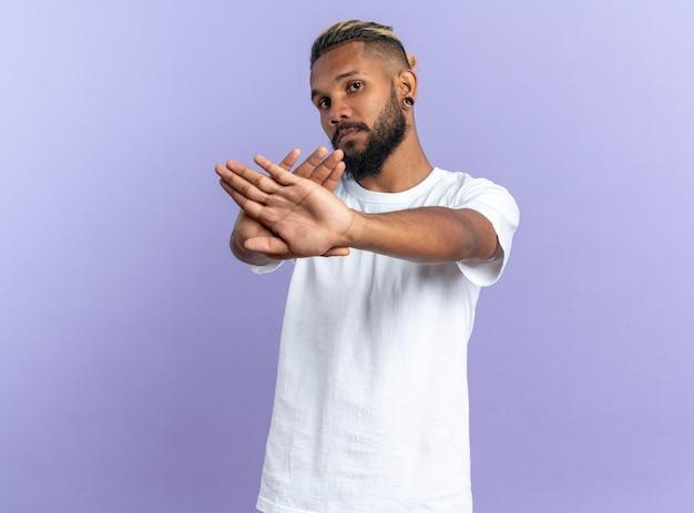 흰색 티셔츠를 입은 아프리카계 미국인 청년은 진지한 얼굴로 카메라를 쳐다보며 파란색 배경 위에 손을 들고 정지 제스처를 취합니다.