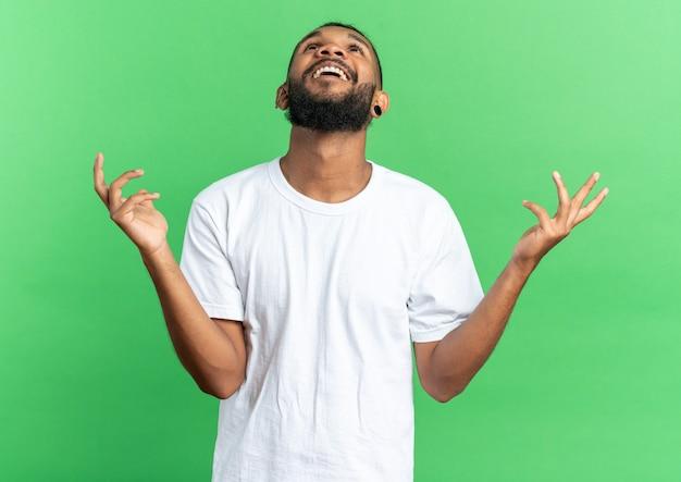 흰색 티셔츠를 입은 아프리카계 미국인 청년이 녹색 배경 위에 서 있는 행복하고 흥분된 팔을 올려다보고 있습니다.