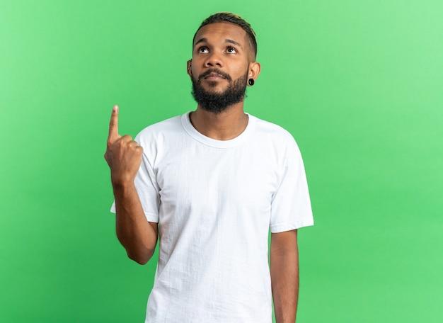 Афро-американский молодой человек в белой футболке смотрит вверх с серьезным лицом, указывая указательным пальцем на что-то стоящее на зеленом фоне