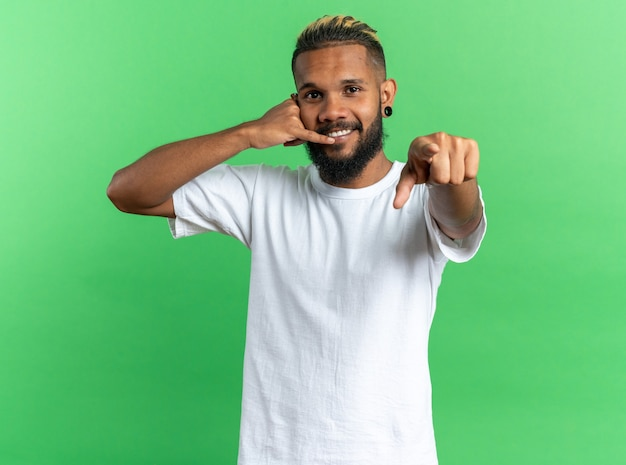 흰색 티셔츠를 입은 아프리카계 미국인 청년은 카메라를 검지 손가락으로 가리키며 녹색 배경 위에 친절한 미소를 지으며 나를 부르는 제스처를 취했습니다.