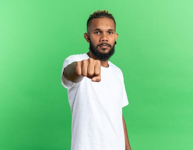 흰색 티셔츠를 입은 아프리카계 미국인 청년은 녹색 배경 위에 서 있는 진지한 자신감 있는 표정으로 카메라를 향해 주먹을 날리고 있습니다.