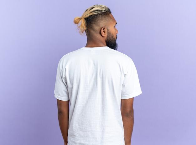 파란색 배경 위에 등을 대고 서 있는 흰색 티셔츠를 입은 아프리카계 미국인 청년