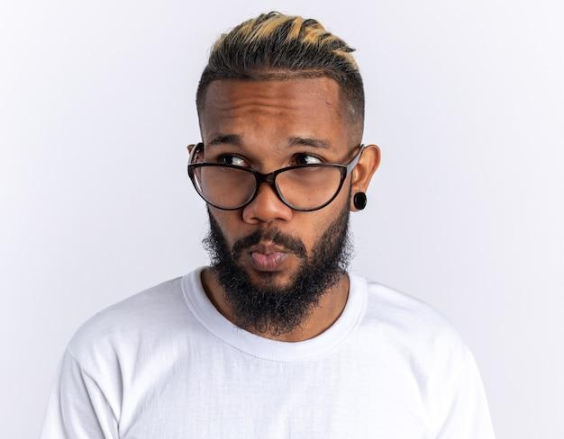 白の上に立って困惑して脇を見て眼鏡をかけている白いtシャツのアフリカ系アメリカ人の若い男