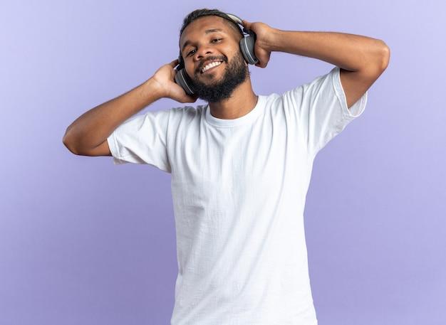흰색 티셔츠를 입은 아프리카계 미국인 청년, 헤드폰을 끼고 파란색 배경 위에 서 있는 좋아하는 음악을 즐기고 긍정적인