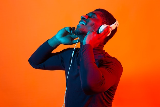 African american young man listening to music online dancing and singing with headphones, neon light