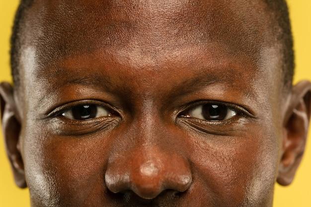 Афро-американский молодой человек крупным планом портрет на желтом фоне студии. красивая мужская модель с ухоженной кожей. понятие человеческих эмоций, выражения лица, продаж, рекламы. глаза и щеки.
