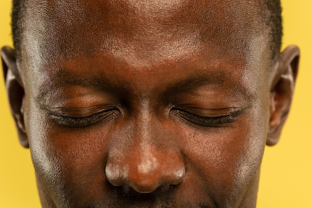 African-american young man's close up portrait on yellow studio background. beautiful male model with well-kept skin. concept of human emotions, facial expression, sales, ad. eyes and cheeks.