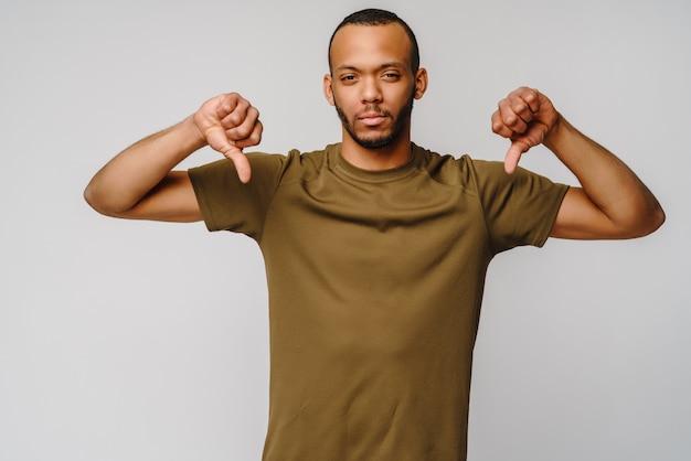 Афро-американский молодой человек показывает большой палец вниз знак с негативным грустным выражением лица над светло-серой стеной