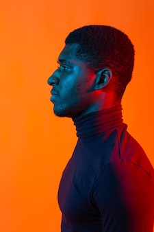 African american young man side portrait with neon light.