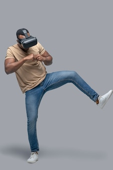 African american young man in vr glasses looking involved