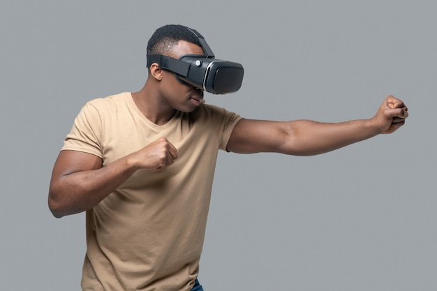 African american young man in vr glasses playing and boxing