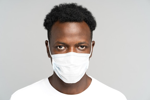 African american young man wearing face medical mask, looking at camera, isolated on grey background