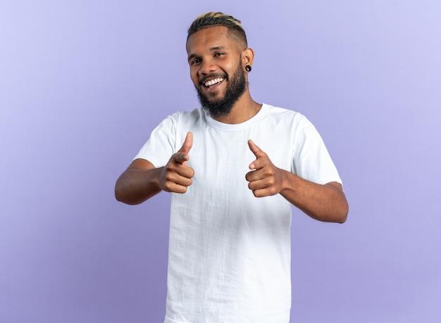 Giovane afroamericano in maglietta bianca felice e allegro che guarda la telecamera sorridente che punta con l'indice alla telecamera