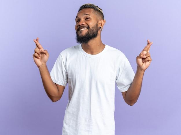 Giovane afroamericano in maglietta bianca allegro e allegro che cerca di rilassarsi facendo un gesto di meditazione con le dita