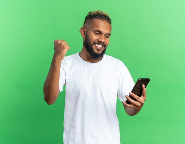 Giovane afroamericano con una maglietta bianca che tiene in mano uno smartphone che stringe il pugno felice ed eccitato che si rallegra del suo successo