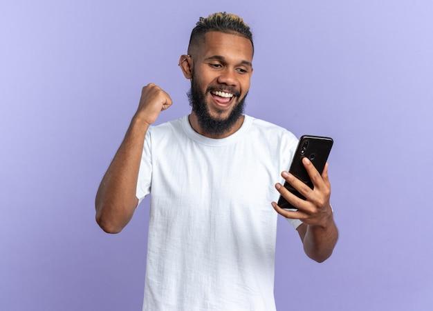 Giovane afroamericano in maglietta bianca che tiene il pugno serrato dello smartphone felice