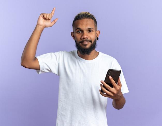 Giovane afroamericano in maglietta bianca che tiene in mano uno smartphone che mostra il dito indice che guarda l'obbiettivo felice e fiducioso una nuova idea concept