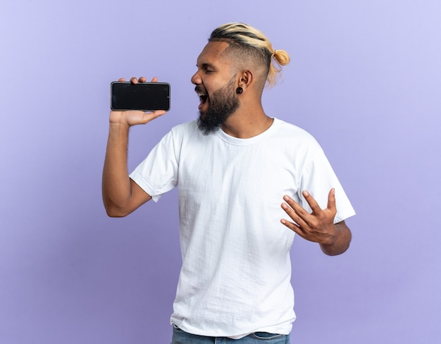 African american young man in white t-shirt holding smartphone using as microphone singing happy and emotional