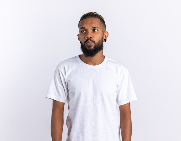 African american young man in white t-shirt looking aside puzzled standing over white background
