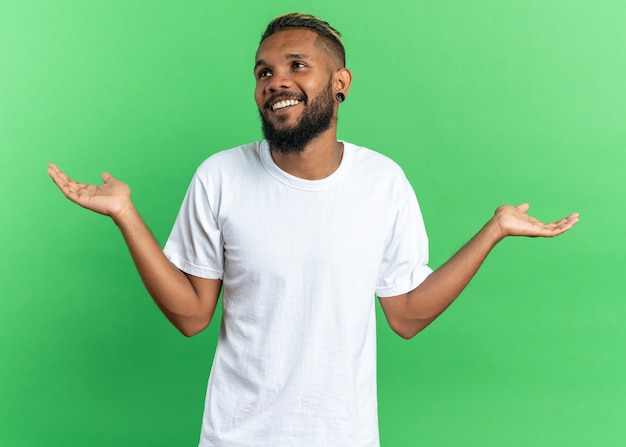 African american young man in white t-shirt looking aside smiling broadly spreading arms to the sides standing over green background
