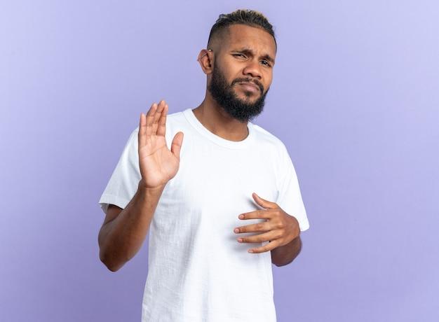 Giovane afroamericano in maglietta bianca che guarda l'obbiettivo confuso e dispiaciuto facendo gesto di arresto con le mani in piedi su sfondo blu