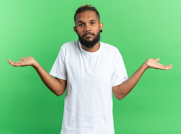 African american young man in white t-shirt looking at camera confused spreading arms to the sides having doubts standing over green background