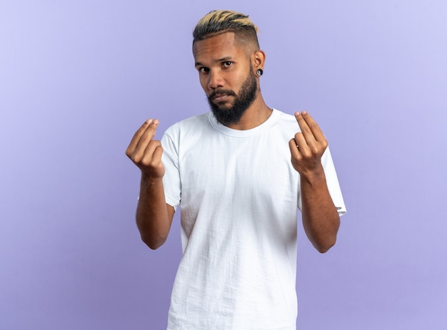 African american young man in white t-shirt looking at camera making money gesture rubbing fingers standing over blue background