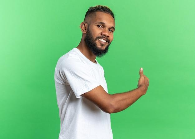 Giovane afroamericano in maglietta bianca che guarda l'obbiettivo sorridendo allegramente puntando indietro con il dito in piedi su sfondo verde