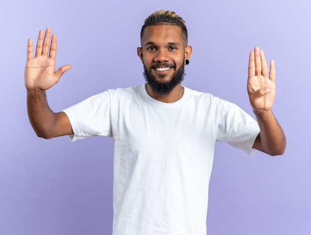 African american young man in white t-shirt looking at camera smiling cheerfully showing number nine standing over blue background