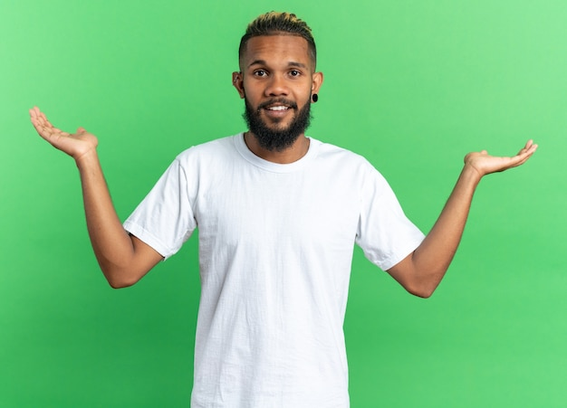 African american young man in white t-shirt looking at camera smiling cheerfully spreading arms to the sides standing over green background