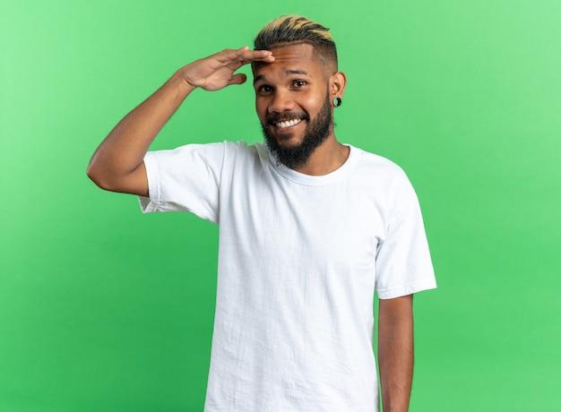 Giovane afroamericano in maglietta bianca che guarda l'obbiettivo sorridente con la mano sulla fronte in piedi su sfondo verde