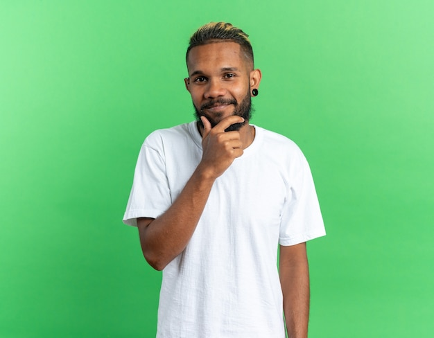 Giovane afroamericano in maglietta bianca che guarda l'obbiettivo con la mano sul mento sorridendo allegramente in piedi su sfondo verde