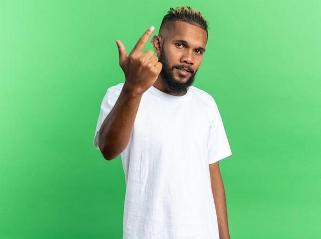 Giovane afroamericano in maglietta bianca che guarda la telecamera con una faccia seria che mostra il dito indice in piedi su sfondo verde
