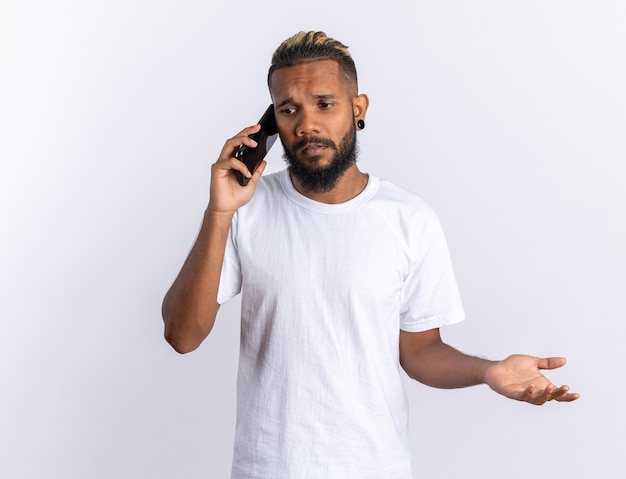 Giovane afroamericano in maglietta bianca che sembra confuso mentre parla al telefono cellulare in piedi su sfondo bianco