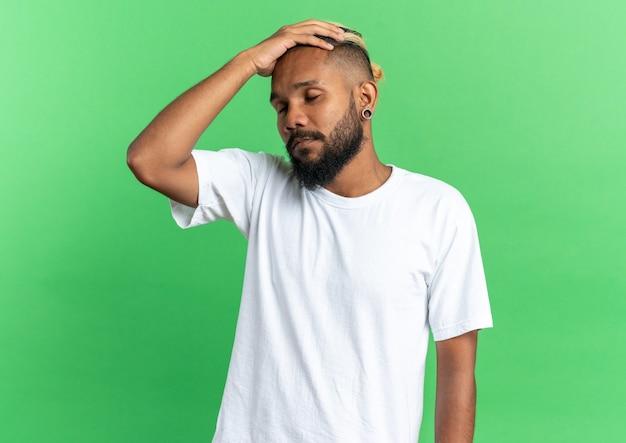 Giovane afroamericano in maglietta bianca che sembra depresso malato con la mano sulla testa in piedi su sfondo verde