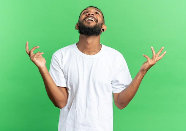 African american young man in white t-shirt looking up happy and excited raising arms standing over green background